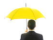 Businessman with yellow umbrella - protection concept.