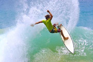 surfer hitting wave lip creates a water curtain spray