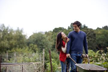 A young couple pushing a wheelbarrow on an allotment