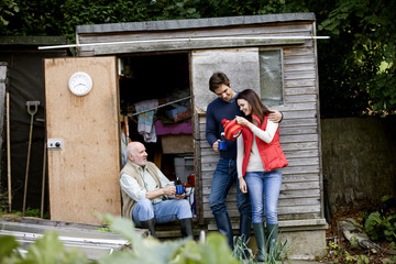A family having a break on an allotment, drinking tea