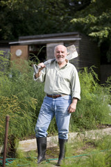 A senior man holding a spade on an allotment