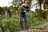 A young man leaning on a fork on an allotment