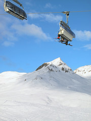 Ski chair-lift with skiers against blue sky. Skiing resort Davos