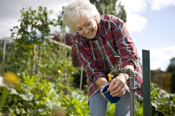 A senior woman washing a cup on an allotment
