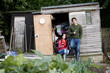 A young couple having a break on an allotment, drinking wine