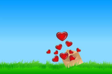 Envelope with hearts on grass