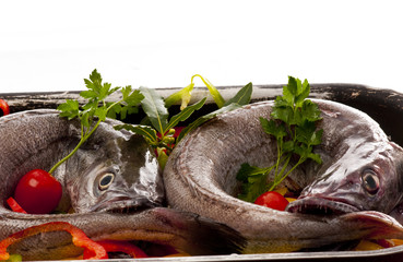 Young hake fish being prepared for cooking with a variety of veg