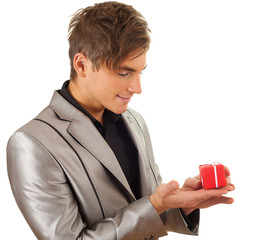 happy young man with small red gift box on palm