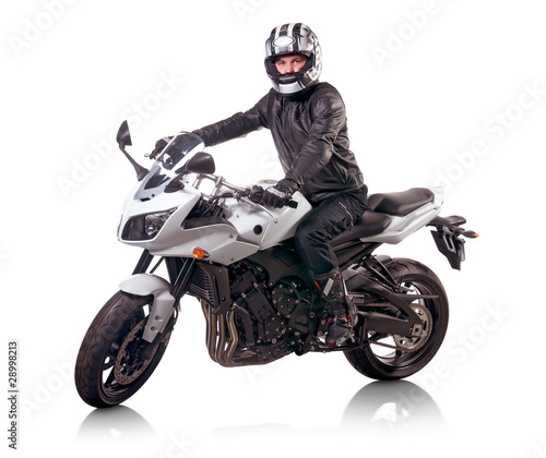 Biker in black leather jacket rides a white motorcycle