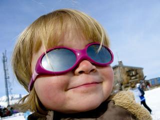 Portait d'enfant au ski avec lunettes de soleil