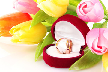 wedding rings and flower bouquet on white