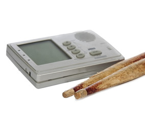 Metronome and drum sticks on white background