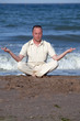 Young businessman doing yoga on a beach