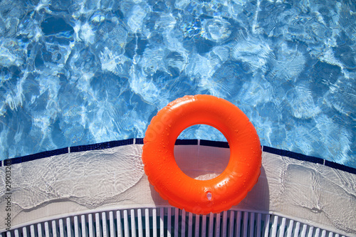 floating orange ring on edge of swimpool with waves reflecting i