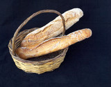 traditional natural yeast bread in a basket, black background poster