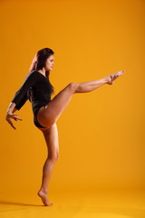 Girl in dance pose right leg extended arms back
