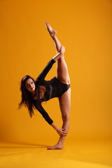 Girl doing standing splits on yellow background