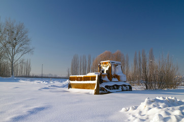 Bulldozer in snowy winter scenery