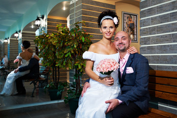 Happy bride and groom on wood bench in modern interior