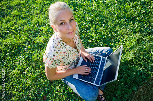 Gorgeous young blond having fun with laptop outdoors