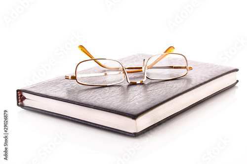 Notebook with glasses isolated on white