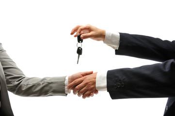 Car dealer giving keys of a new car to female buyer.