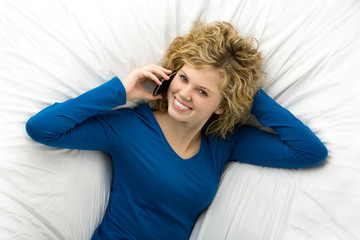 Beautiful teenage girl lying down talking on cell phone