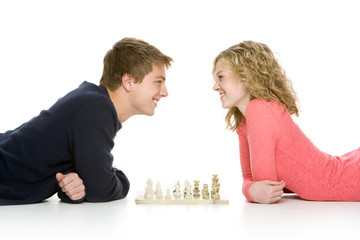 Attractive teenagers lying down playing chess, isolated on