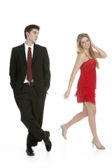 Attractive teenage girl in a red dress walking past teenage boy
