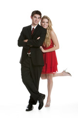 Teenage couple dressed in formal clothing standing close togethe
