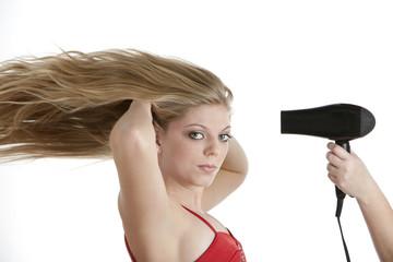 Beautiful teenage girl having her hair blow dried