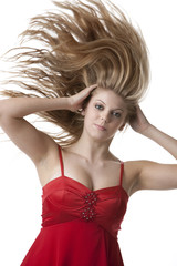 Beautiful blonde teenage girl with flying hair isolated on white