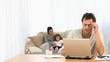 Angry man on his laptop while his family is on a sofa