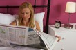 Blonde girl lying in bed reading a newspaper