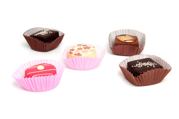 five delicious pink petit four over white background