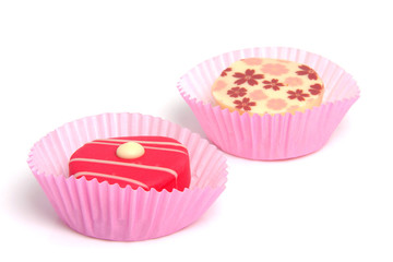 two delicious pink petit four over white background