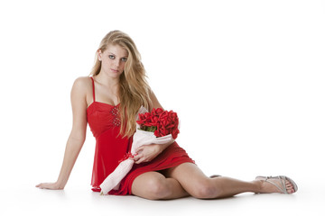 Attractive teenage girl in a red dress holding a bouquet of rose