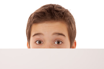 Junge schaut neugierig über ein weißes Schild