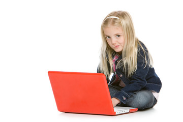 Cute little girl sitting with laptop