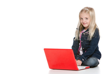 Cute little girl sitting down with laptop in studio