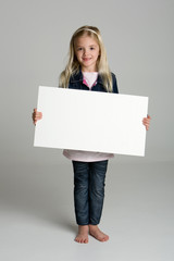 Little girl isolated on neutral background holding a blank sign