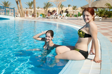 girls in  swimming pool at resort hotel
