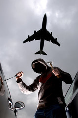 Car thief breaking in to car parked at airport, plane overhead