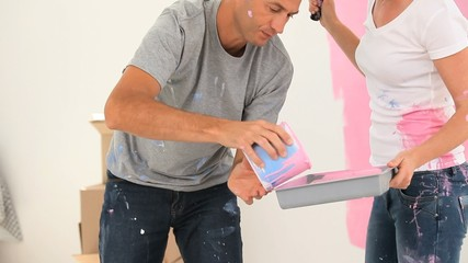 Man helping his girlfriend to paint