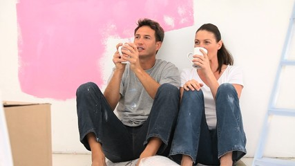 Couple having a coffee break during a renovation in a room
