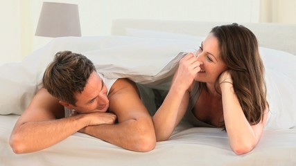 Pretty couple talking in their bed