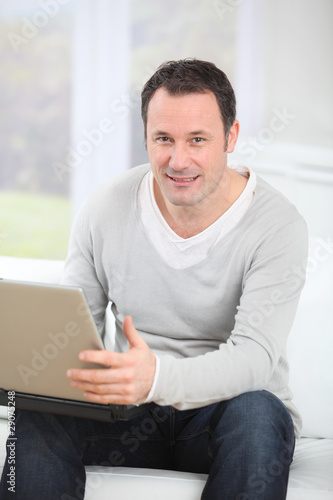 Man sitting in couch using laptop computer