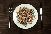 Płyta z bolcem papierosów z sztućce na biurku drewna