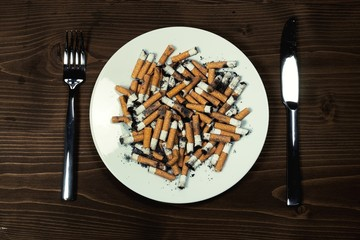 Plate with cigarettes stub with cutlery on wood desk