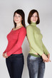 two young brunette girls in red and green shirts standing back t